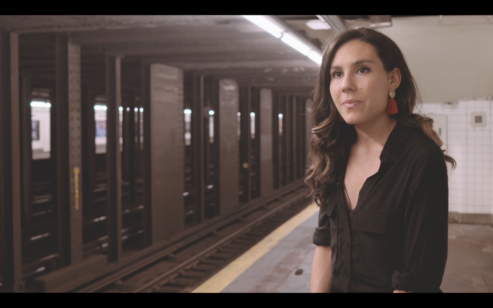A screenshot from a film real, a woman speaking to someone off camera with the subway as a background