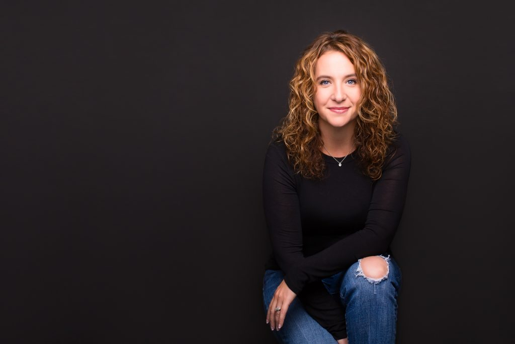 A woman, Jennifer Cloer, kneeling and smiling at the camera