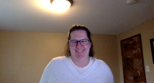 Smiling woman in white shirt and glasses in Zoom videoconferencing screenshot