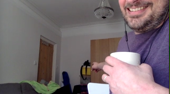 Man's face cut off as he smiles holding a mug and pointing to an overcrowded room's doors in a Zoom videoconferencing screenshot