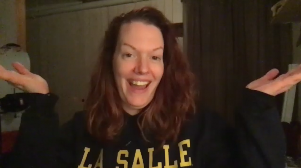 Woman in a hoodie smiling from a dark basement with her hands out presenting in a Zoom videoconferencing screenshot