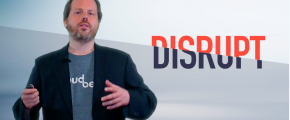 The CEO is standing and speaking in front of the word: Disrupt