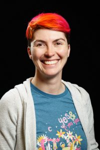 Headshot of a 30-something woman with bright orange and pink hair smiling at the camera in a blue tshirt with flowers and a beige cardigan.