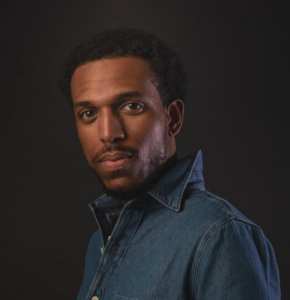 headshot of a 30-something Black man in a denim button-down shirt looking at the camera