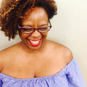 A photo of Kim, a Black woman with red lipstick and a purple blouse laughing with her whole heart