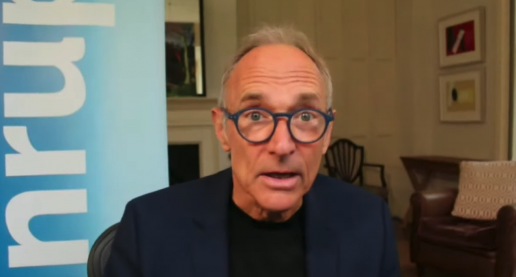 65-year-old Tim Berners Lee with round glasses and a rather surprised look in what looks like his living room with an Inrupt banner