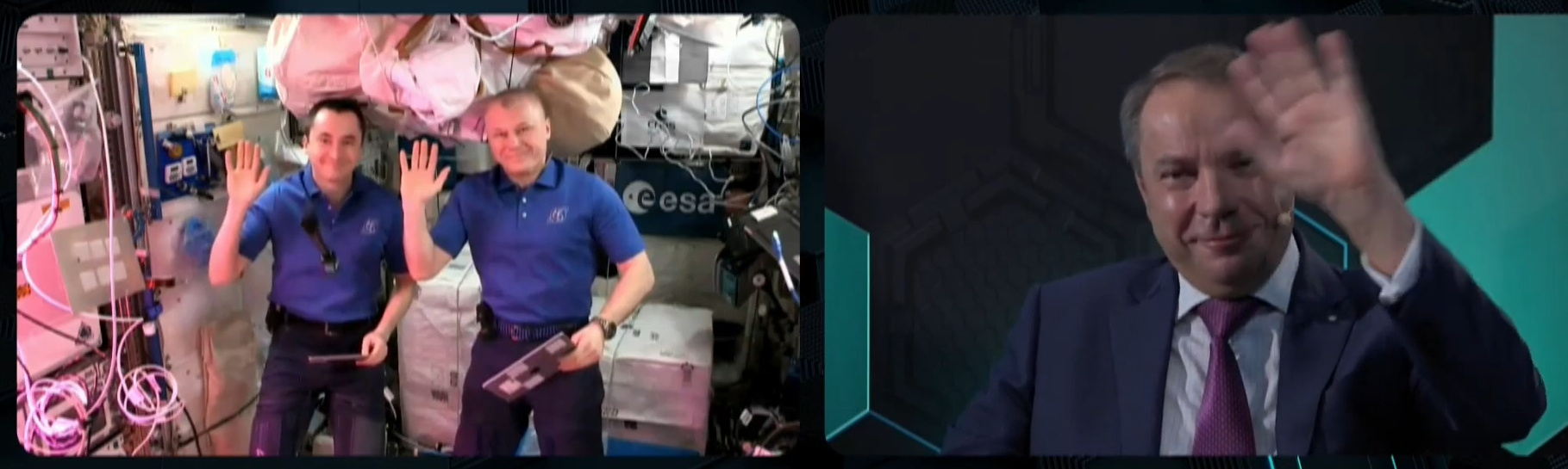 Waving with floating microphone between Pyotr Dubrov (left) with Oleg Novitskiy during ISS interview for Cyber Polygon 2021 (screenshot via YouTube video)